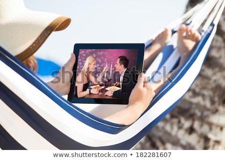woman lying on hammock watching video on digital tablet stock photo © andreypopov