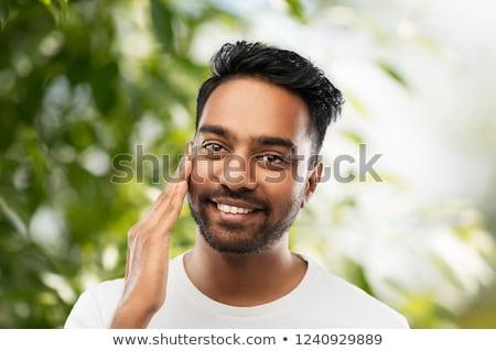 smiling indian man touching his face Stock photo © dolgachov