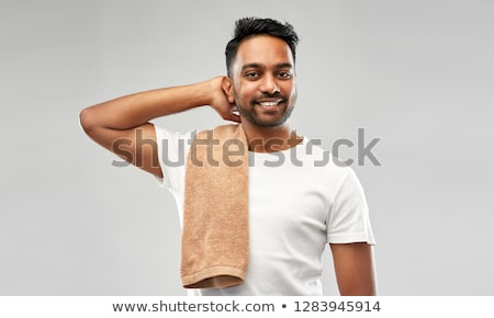 smiling indian man with towel over grey background stock photo © dolgachov