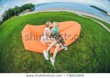 Mother and son resting on an air sofa in the park. Stock photo © galitskaya