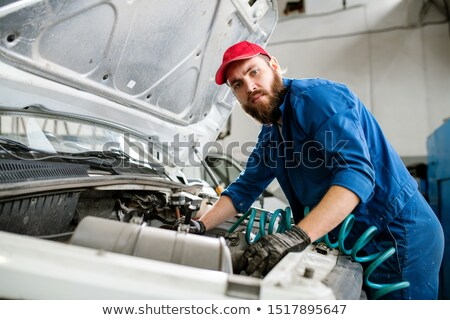 Serious technician looking at you while repairing engine of broken machine Stock photo © pressmaster