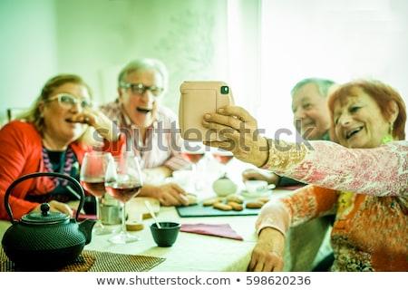 happy couple with smartphone at family tea party Stock photo © dolgachov