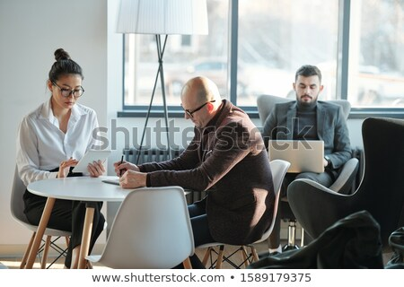 Group of intercultural busy co-workers in formalwear working in hotel lounge Stock photo © pressmaster