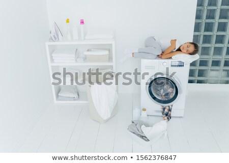 Shot of tired small kid sleeps on washing machine, uses white soft towel as pillow, has pleasant dre Stock photo © vkstudio