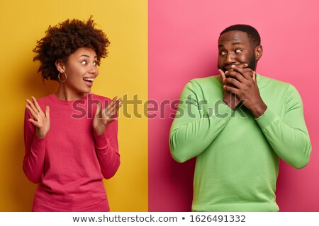 Positive unshaven man covers mouth with palm, giggles positively, wears spectacles, hears funny joke Stock photo © vkstudio