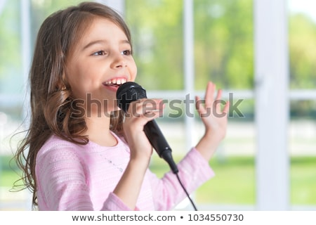 Beautiful blonde girl singing to music at home Stock photo © darrinhenry