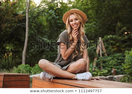 Woman with long blonde hair sitting on a bench stock photo © photography33
