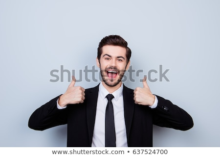 Young male giving thumbs up against a white background stock photo © wavebreak_media