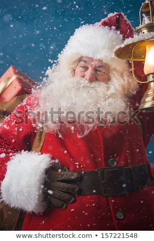 Santa Claus outdoors in snowfall lights the way with vintage lan Stock photo © HASLOO