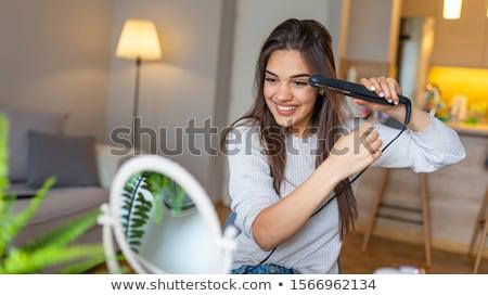 Cute woman holding hair straightener  Stock photo © deandrobot