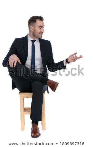 businessman posing in studio background seated while talking on stock photo © feedough