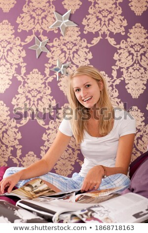 Adult woman smiling at camera while holding magazine Stock photo © d13