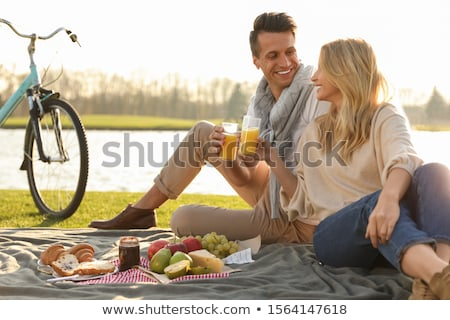A young couple having a picnic by a lake Stock photo © IS2