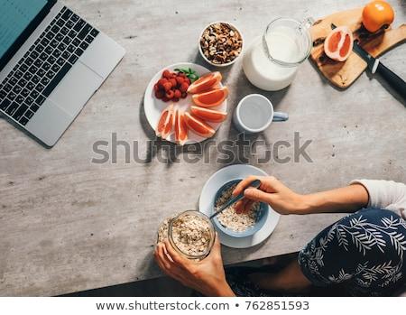 Jonge vrouw eten grapefruit tabel ontbijt vrouwelijke Stockfoto © IS2