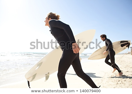 two men running into the water with surf stock photo © is2