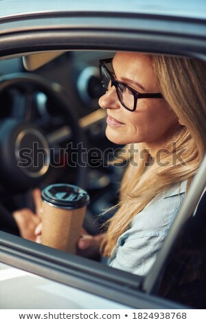 Stock photo: Businesswoman holding takeaway coffee cup in car