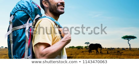 close up of man with backpack over savannah Stock photo © dolgachov