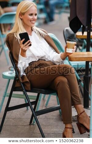 Image of elegant woman wearing jacket holding takeaway coffee in Stock photo © deandrobot