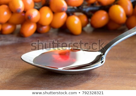 Sea buckthorn oil on a spoon with fresh sea buckthorn berries Stock photo © madeleine_steinbach