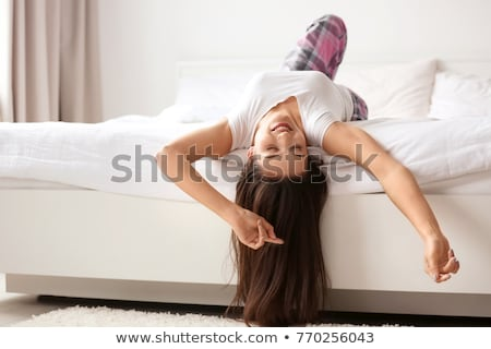 Happy smiling woman upside down in bed in the bedroom Stock photo © galitskaya