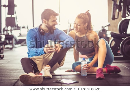 Young woman and personal trainer rest in the gym after workout stock photo © boggy