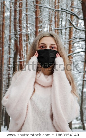Woman in a snowy woodland of pine trees Stock photo © lovleah