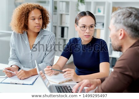 Two young intercultural female subordinates consulting with their boss Stock photo © pressmaster