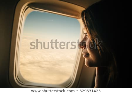 Businesswoman traveling in airport. Woman looking through the window at tarmac and planes waiting fo Stock photo © Maridav