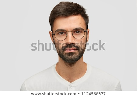 Image closeup of young bearded man standing over white wall indo Stock photo © deandrobot