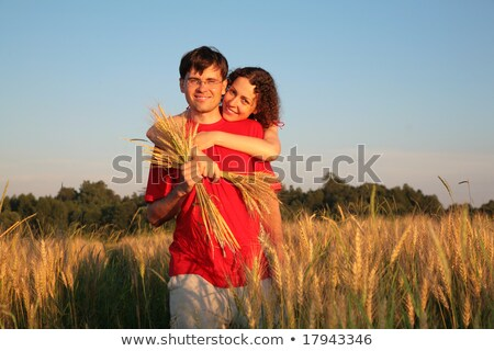 young woman embraces man behind on wheaten field Stock photo © Paha_L