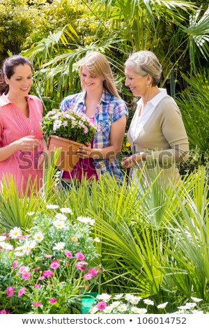three friends in shop holds pots with plants in shop stock photo © paha_l