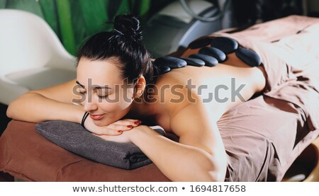 Woman having a hot stone therapy session Stock photo © Kzenon
