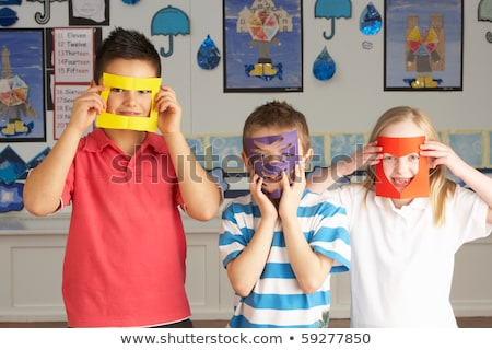 Male Primary School Pupil Cutting Out Paper Shapes In Craft Less Stock photo © monkey_business