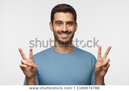 handsome man showing the victory gesture. stock photo © feedough