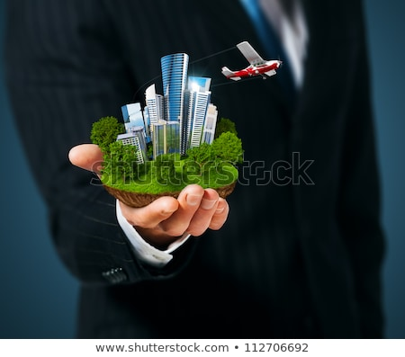 hand holds city of skyscrapers on green grass and businessman walking forward flying letters near h stock photo © cherezoff