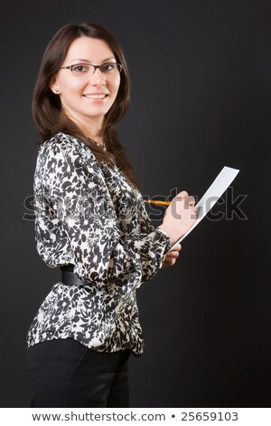 Businesswoman Writing Against Black Background Stock photo © AndreyPopov