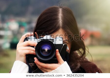 smiling inspired woman photographer taking photos at forest in winter stock photo © deandrobot