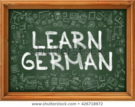 learn german concept green chalkboard with doodle icons stock photo © tashatuvango