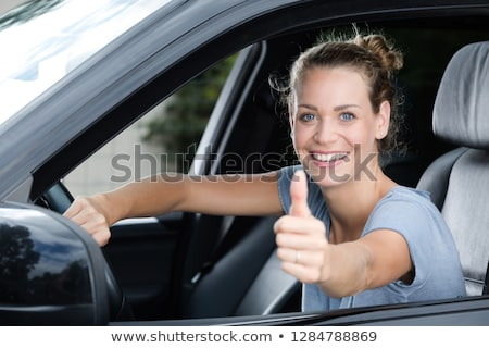 Young happy woman sitting in a car with thumb up Stock photo © vlad_star