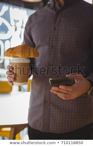 Mid-section of businessman using mobile phone while having a cup Stock photo © wavebreak_media