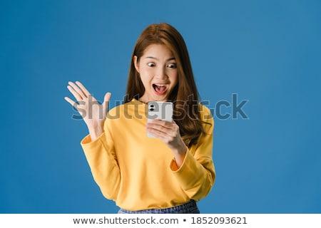 Geschokt jonge vrouw mobiele telefoon foto permanente geïsoleerd Stockfoto © deandrobot