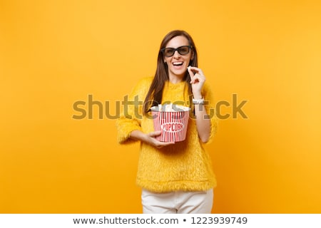 woman in 3D glasses watching a movie, smiling and eating popcorn Stock photo © studiostoks