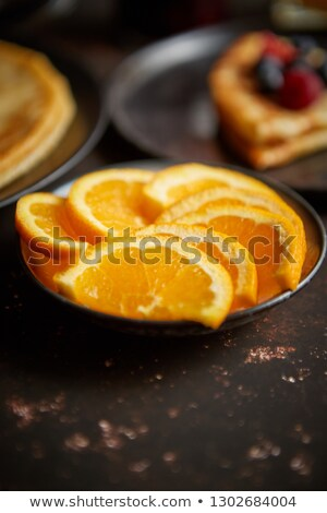Close up on fresh orange slices placed on ceramic saucer Stock photo © dash