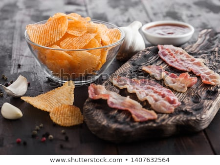 Potato crisps with backon flavour with grilled bacon rashers on vintage chopping board with garlic a Stock photo © DenisMArt