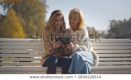 grandmother and granddaughter with tablet at park Stock photo © dolgachov