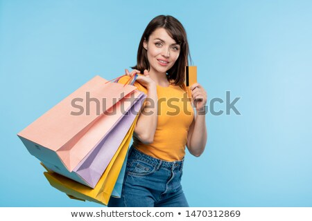 Happy young shopaholic with several paperbags boasting with credit card Stock photo © pressmaster