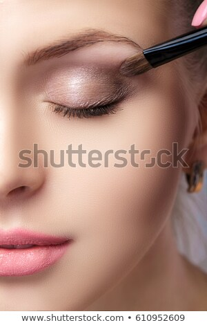 Makeup artist applies eye shadow. Beautiful woman face. Perfect makeup Stock photo © serdechny
