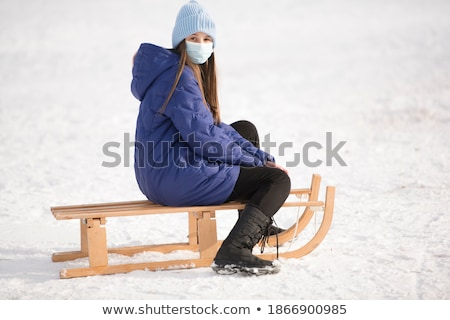 teenage girl riding on sledge in snowy landscape stock photo © monkey_business
