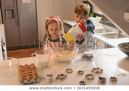 front view of cute siblings trying to make cookies in kitchen at home stock photo © wavebreak_media