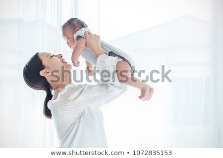 happy little asian baby boy with mother at home stock photo © dolgachov